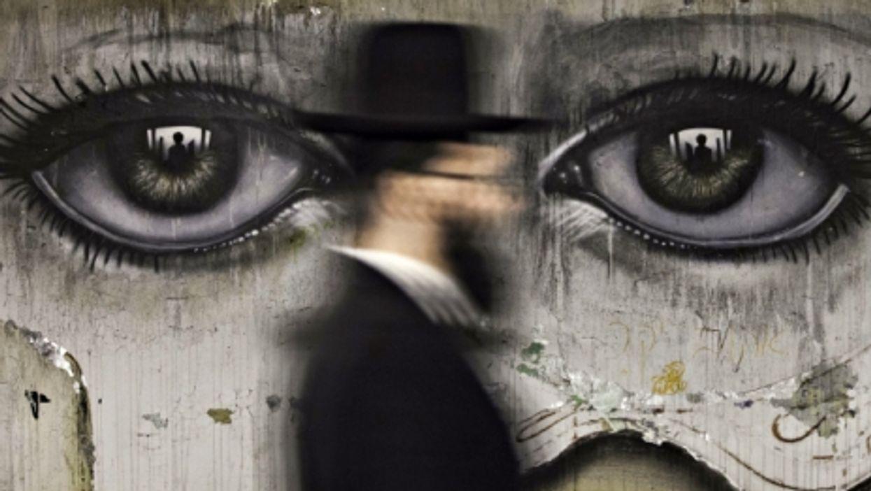 An ultra-Orthodox Jew walks past graffiti in Jerusalem