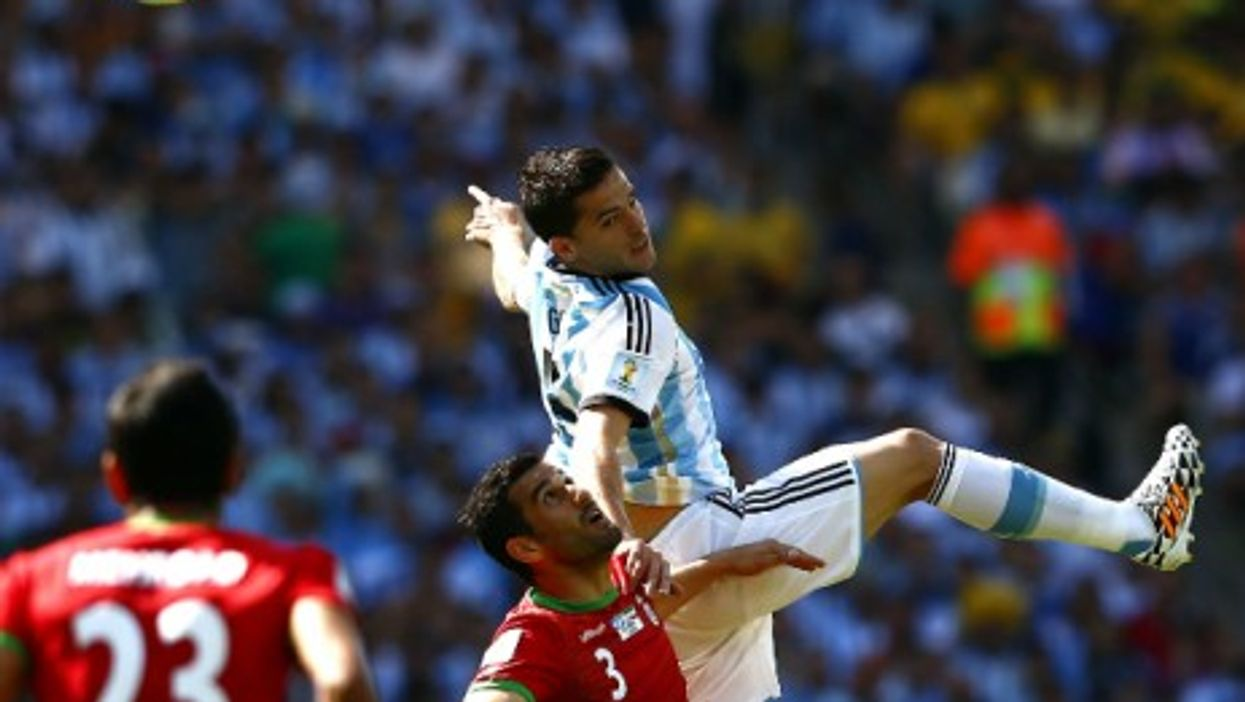 Argentina's Fernando Gago fights for the ball with Iran's Ehsan Hajsafi during a World Cup group match at the Estadio Mineirao Stadium in Belo Horizonte, Brazil, on June 21, 2014.