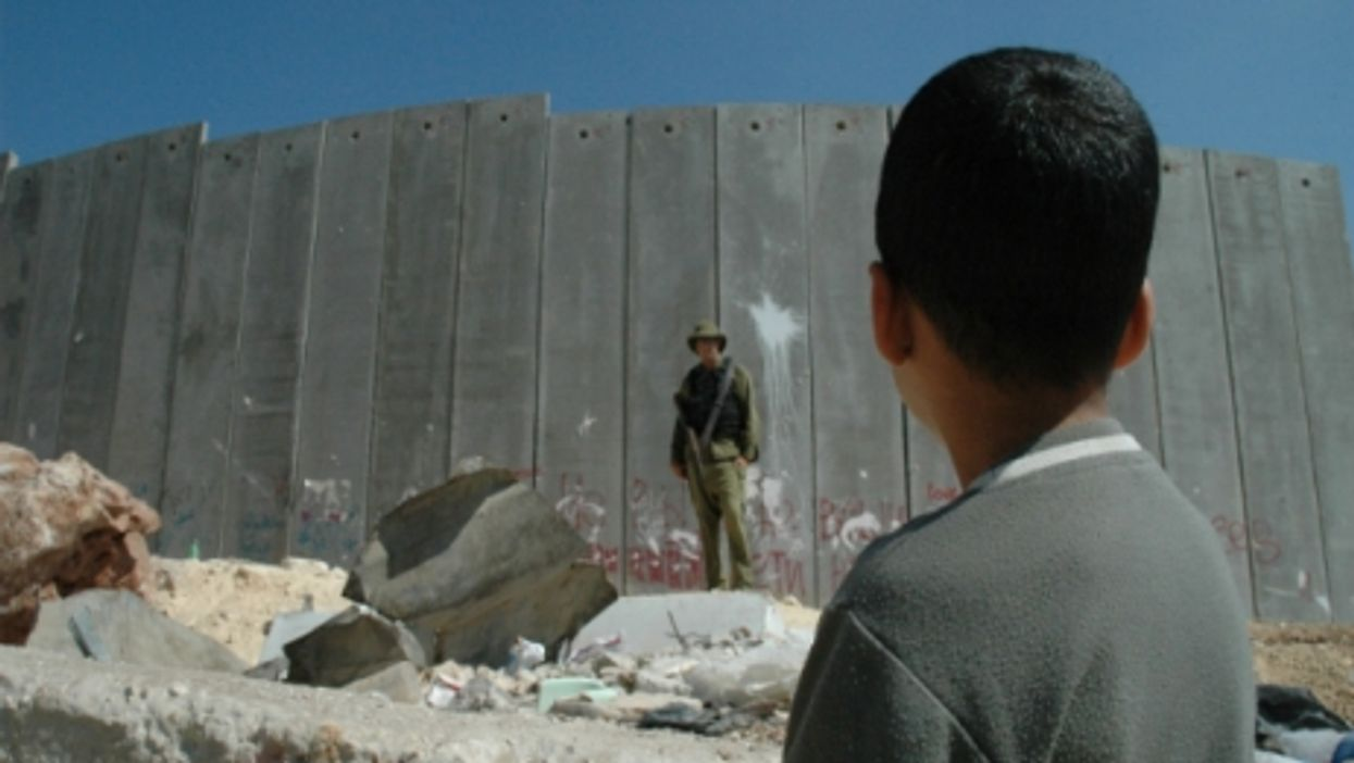 Boy and a soldier at the West Bank wall