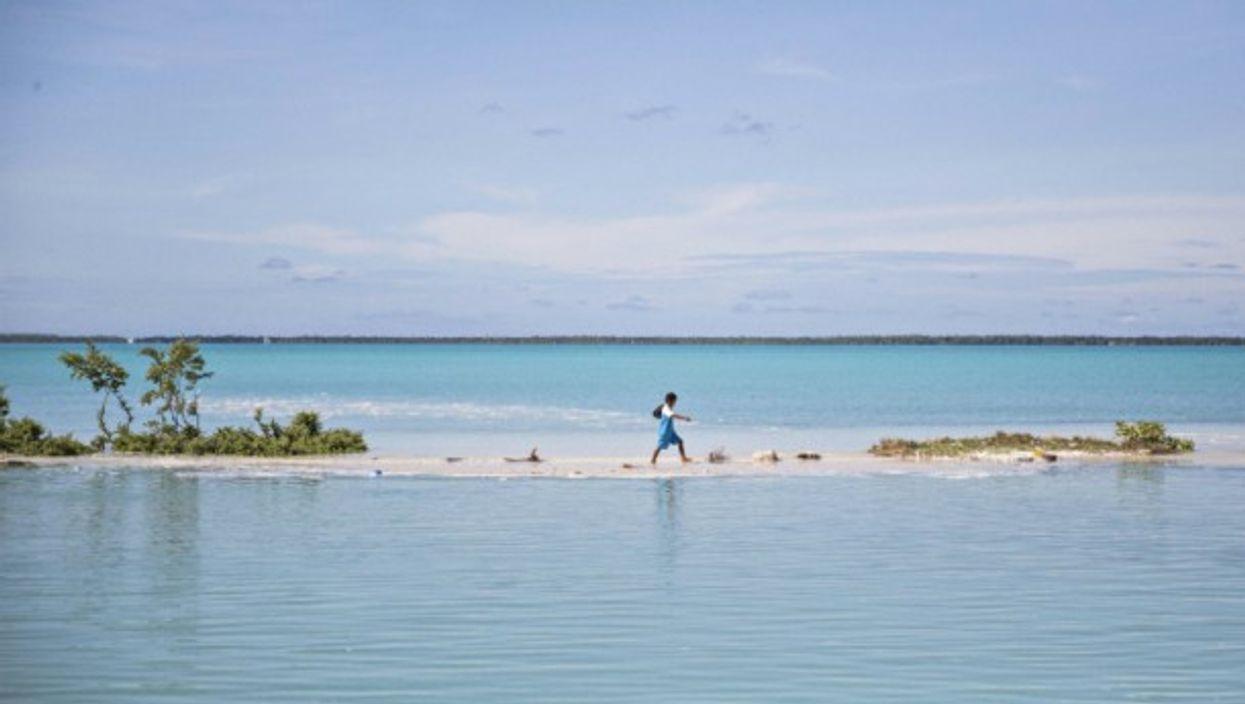 Boy walking to school in Aberao, Kiribati