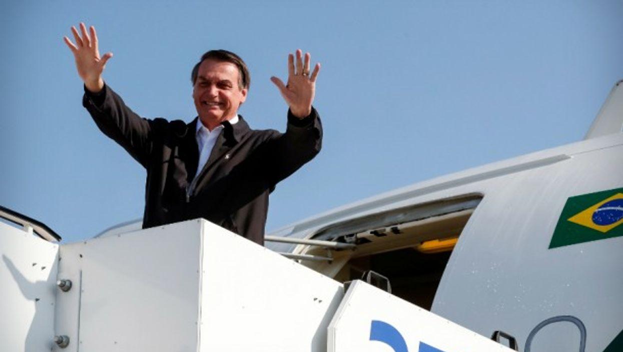 Brazil's President Jair Bolsonaro waving to the crowd as he leaves Israel