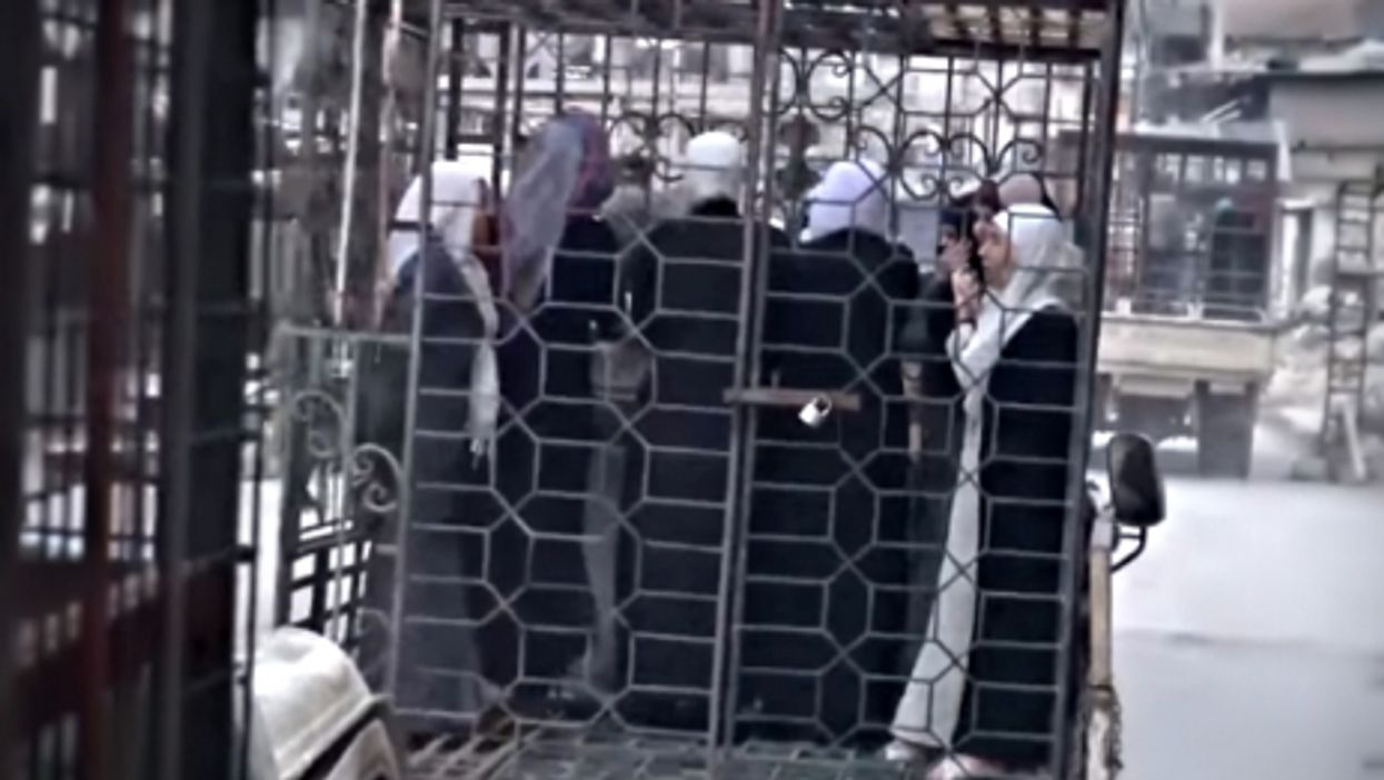 Caged women paraded in Douma