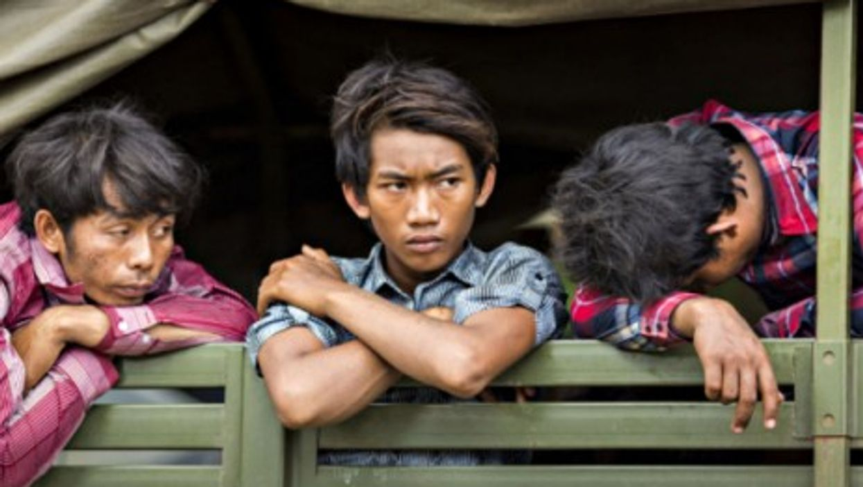 Cambodian migrants wait in an army truck to return home from Thailand.