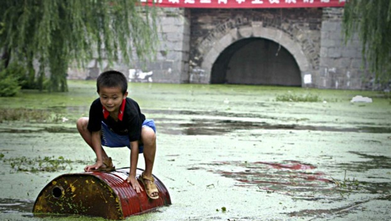 Child playing on garbage floating in the Huai River