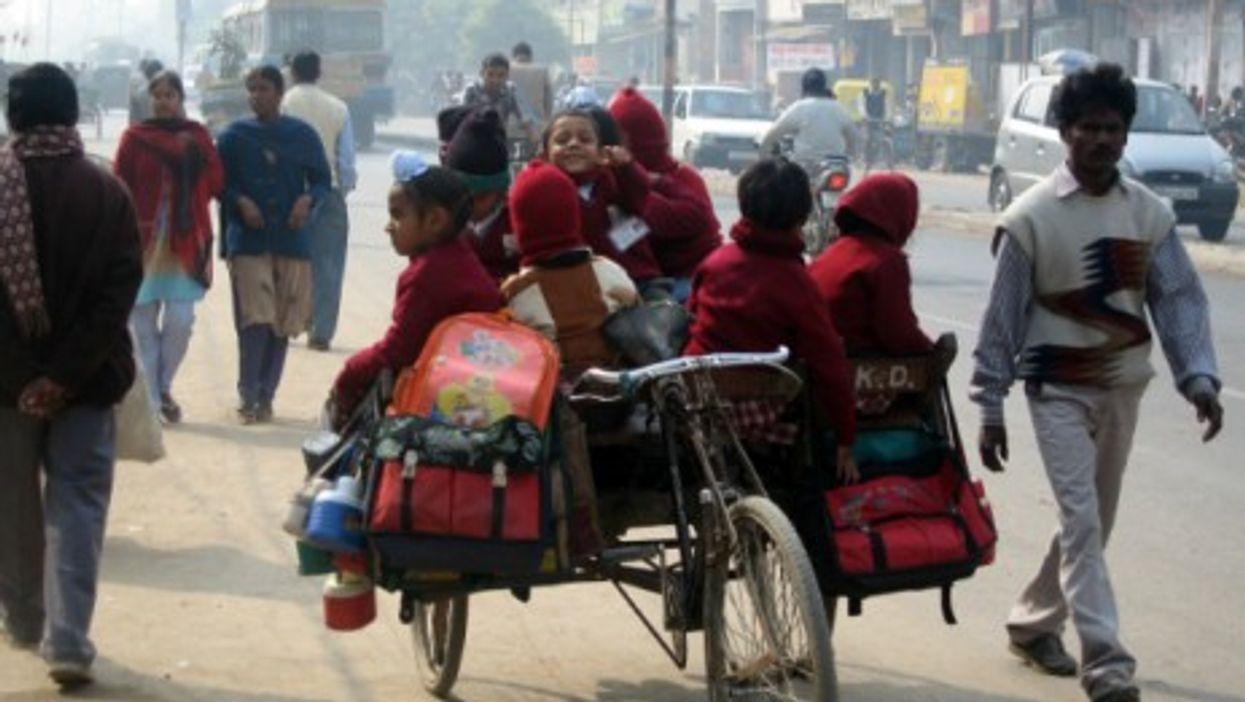 Children go to school on a rickshaw in Lucknow, India