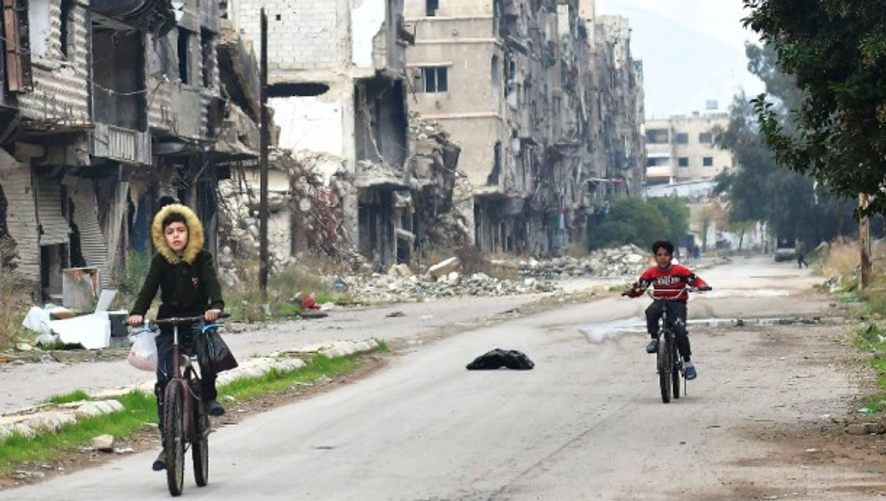 Children ride in the Yarmouk Camp area, south of the capital Damascus
