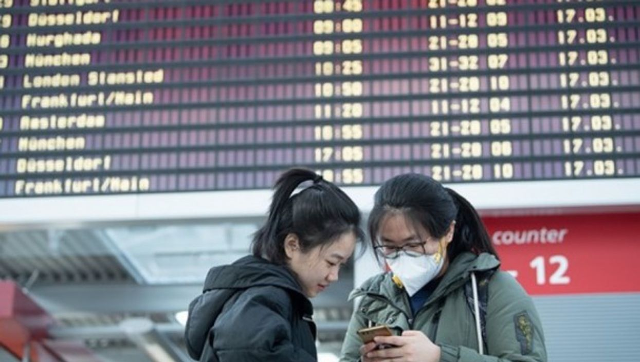 Chinese students in front of a departure board at Dresden Airport, where numerous flights are cancelled due to the coronavirus pandemic.