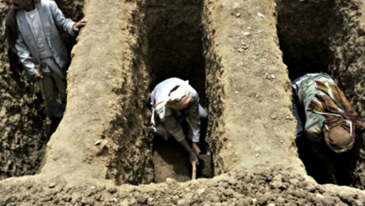Digging graves after a Saudi airstrike in Yemen's Bani Matar district on April 4