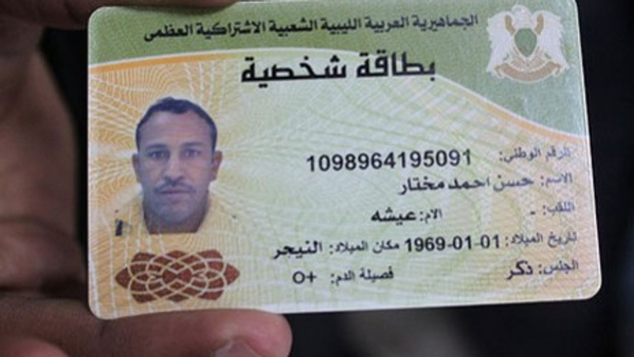 Doctors in Brega, Libya show identity card of a slain pro-Gaddafi fighter they say was a Tuareg from Niger