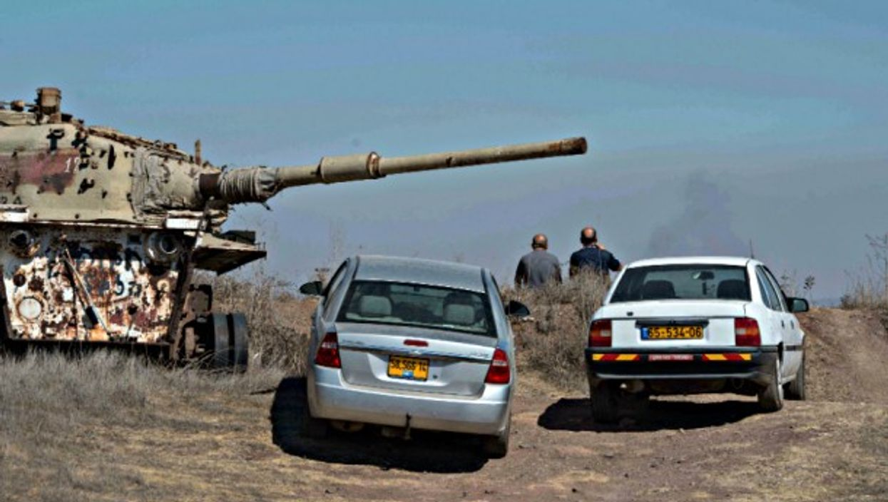 Druze residents watch fighting on the Syrian side of the border from vantage point in Golan Heights