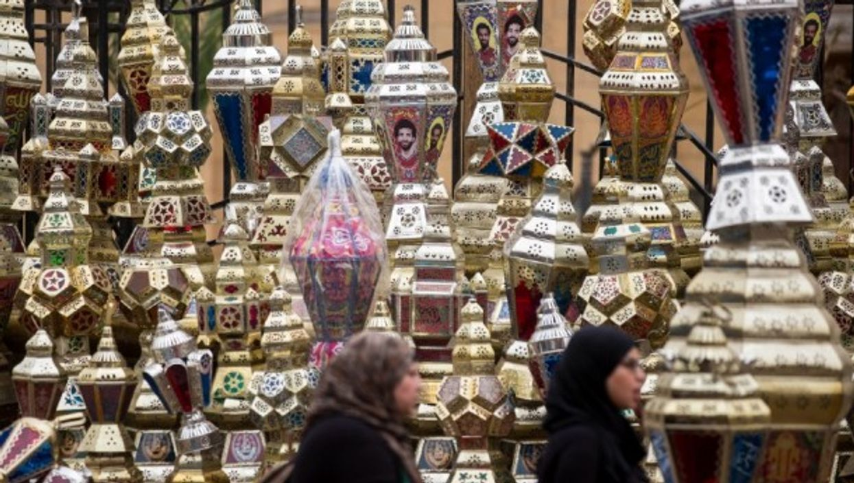 Egyptian women pass by Ramadan lanterns in Cairo, in May 2018.