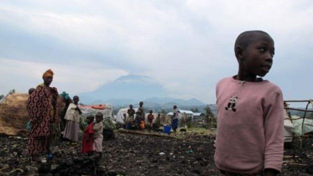 Families look on in the Kanyaruchinya camp