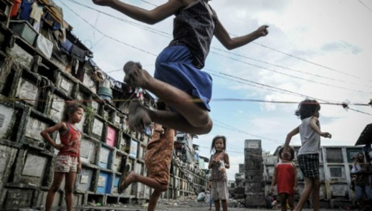 Filipino children playing in a cemetery near Manila as the country prepares for All Saint's Day