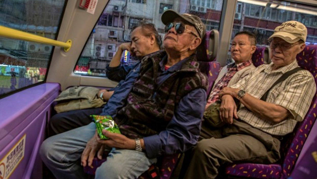 Four elderly men ride the bus home from their day jobs in Hong Kong
