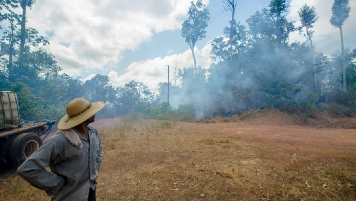Framer Ita watches as smoke rises from a fire in the Amazon Rainforest