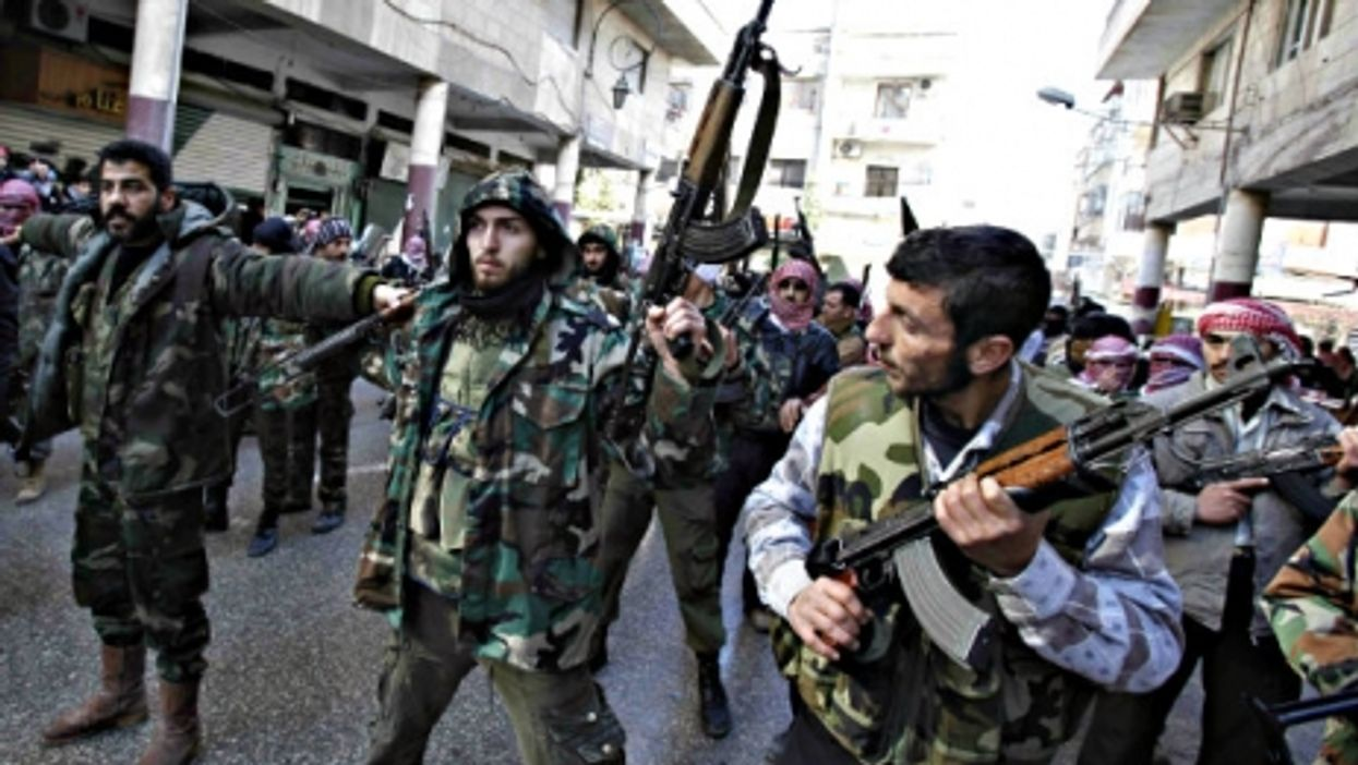 Free Syrian Army (FSA) fighters marching through the streets of Idlib