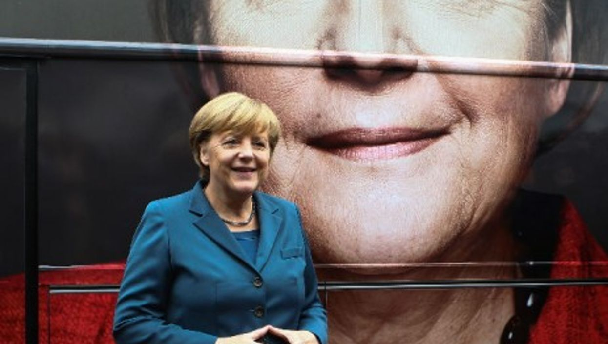German Chancellor Angela Merkel poses in front of her picture on an campaign bus in Berlin, Germany, on Sept. 16, 2013