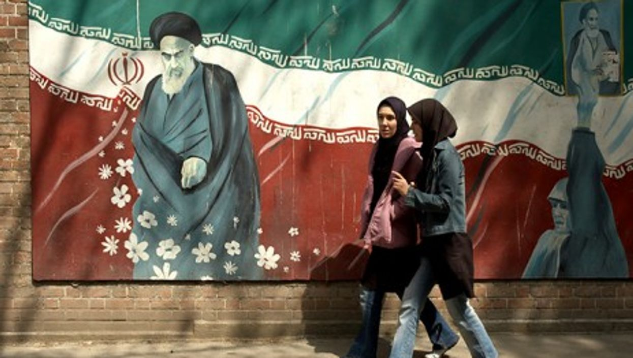 Girls in western jeans walking past a picture of Ayatollah Khomeini in Tehran