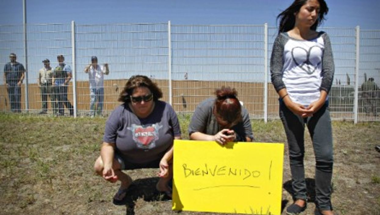 Human rights protesters pray for women and children stopped from entering the Border Patrol facility in Murrieta, CA, on July 1.