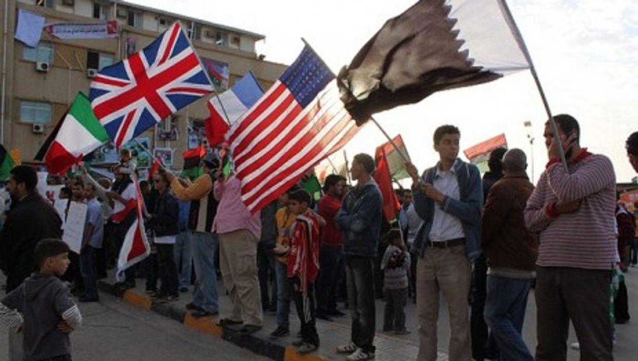 In Benghazi, people holding the Qatari, American, French, British and Italian flags