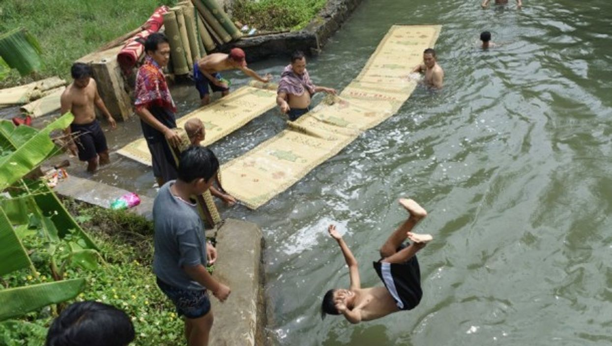 In Semarang, Indonesia, residents wash mosque prayer mats (and have some fun) in a river to purify them, a tradition in preparation for the Ramadan fasting month that will start tomorrow.