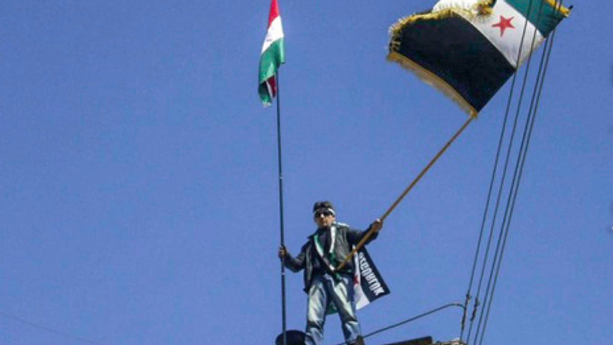 In the Syrian border town of Qamishli, a protester with a Kurdish and Syrian rebel flag (Freedom House)