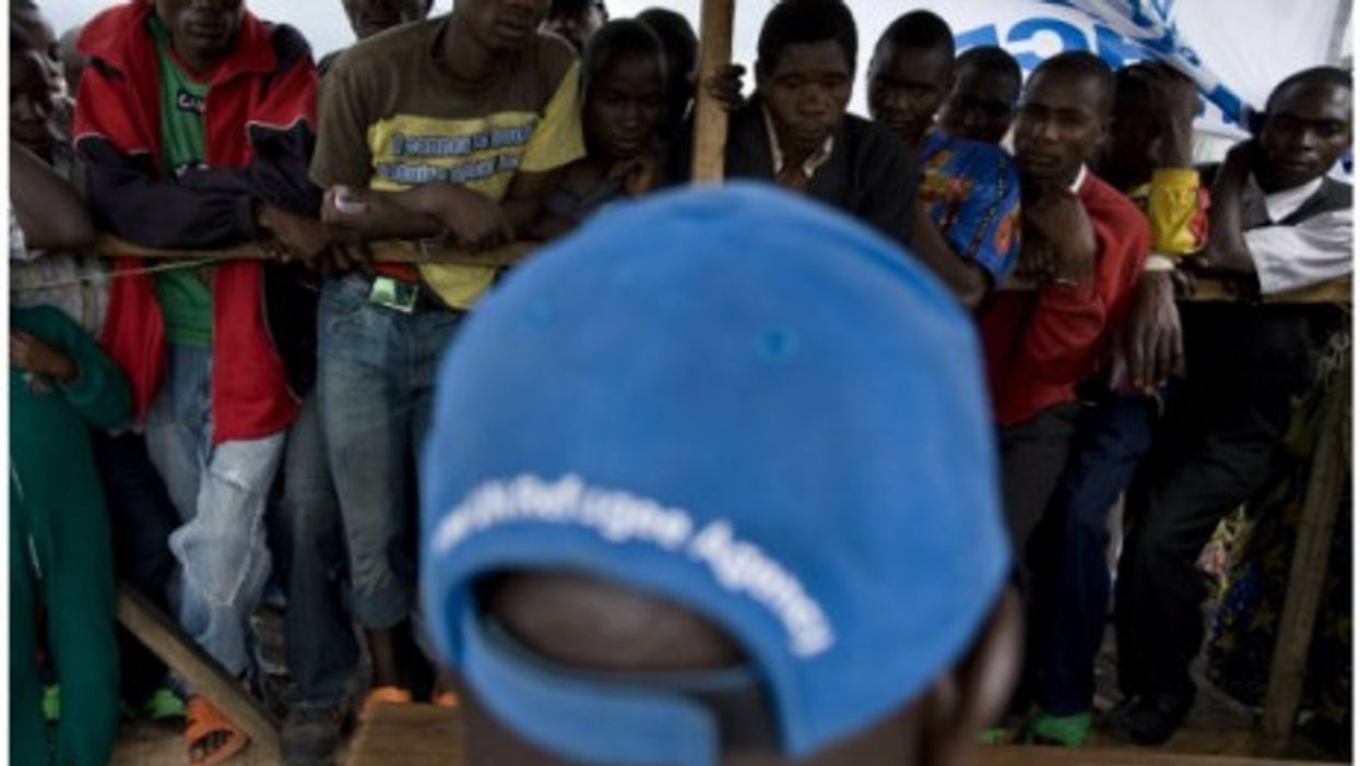 In this file photo in Goma, internally displaced Congolese line up for aid