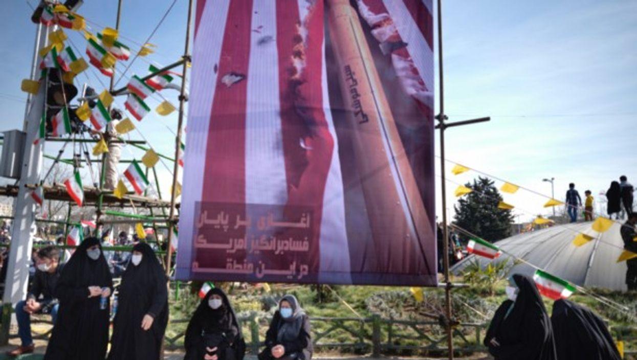 Iranian women under an anti-U.S. banner in Tehran