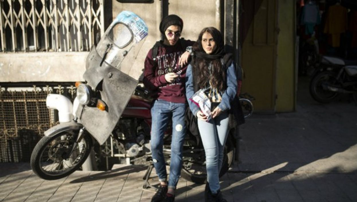 Iranian youth spend time at an alley in downtown Tehran