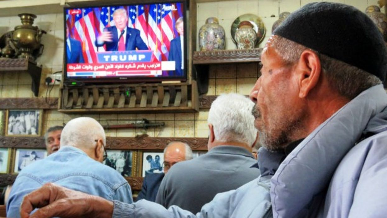 Iraqi men in Baghdad watch television as the newly elected American president speaks.