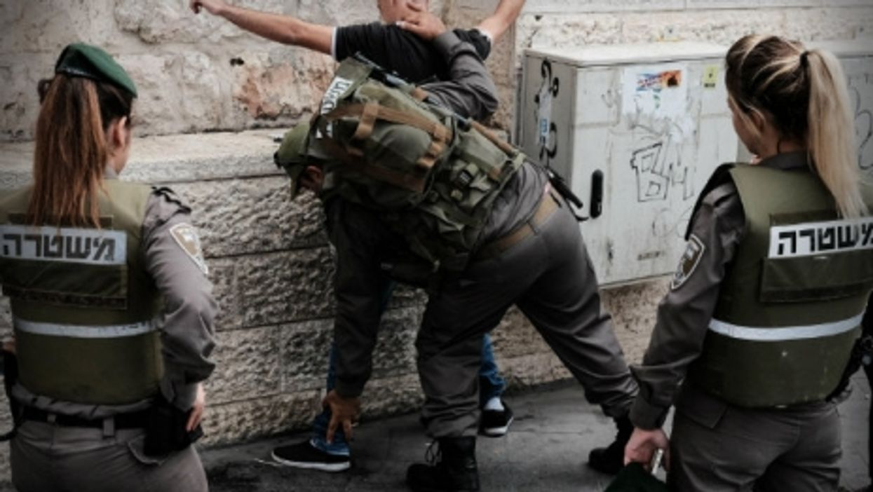 Israeli security forces search a Palestinian youth near the Jerusalem central bus station