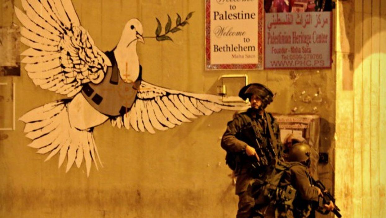 Israeli soldiers next to a Banksy mural in Bethlehem