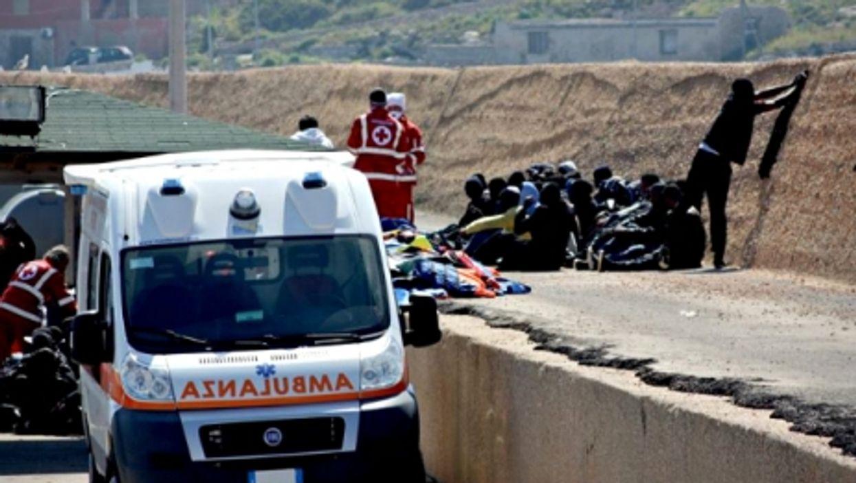 Italian Red Cross members helping migrants in Lampedusa