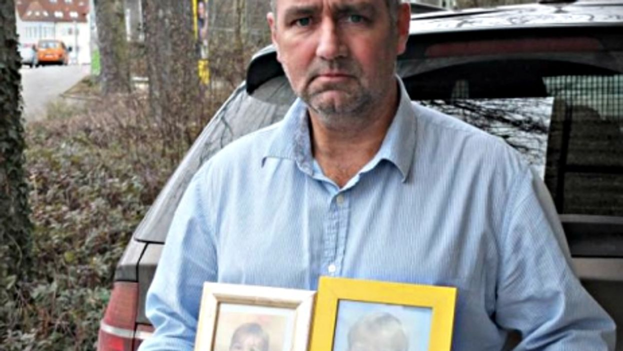 Joachim Gerhard carrying pictures of his two sons
