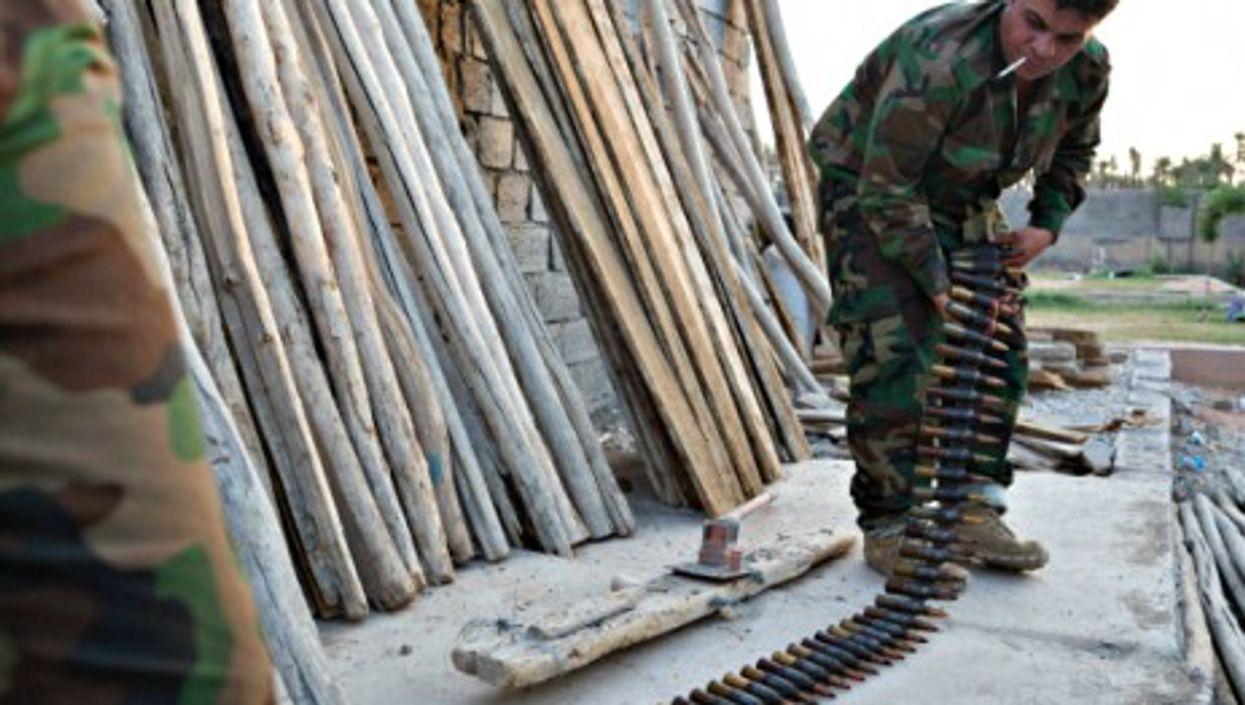 Kurdish peshmerga fighters prepare ammunition for a heavy machine gun at a base in Khanaqin, Iraq.