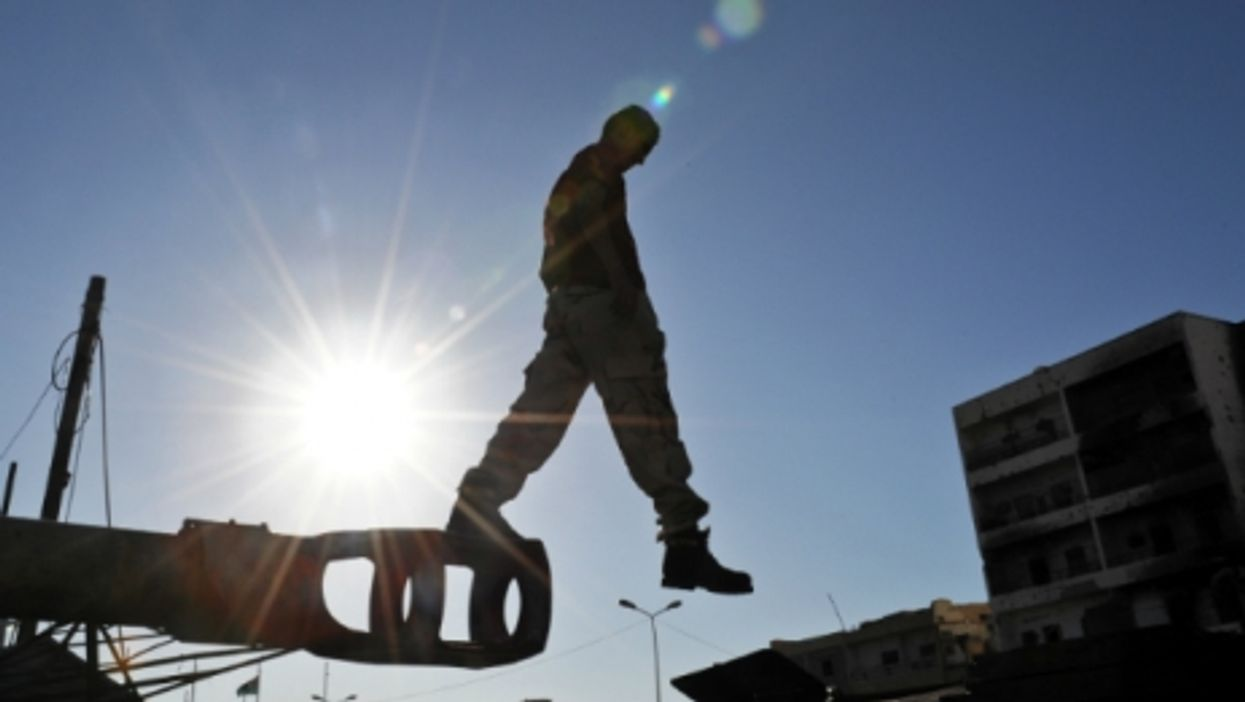 Man jumping off a disused military vehicle in Misrata, Libya