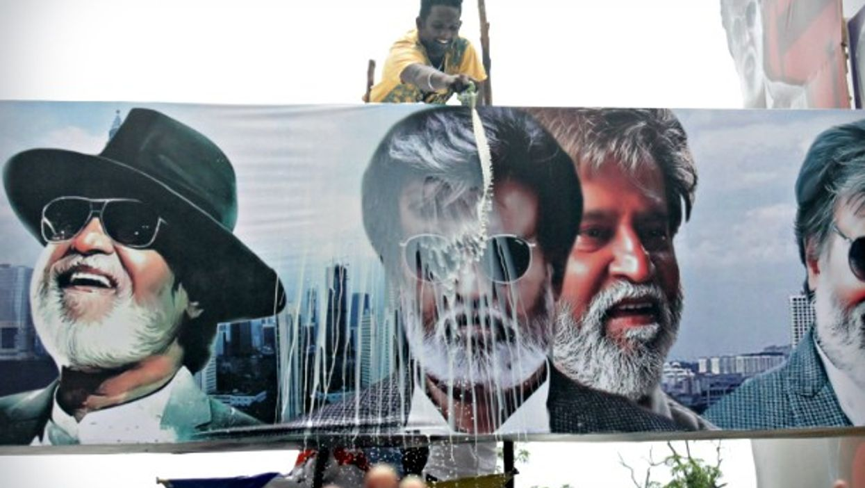 Man ritually pouring milk on a Rajinikanth poster in Chennai on July 22