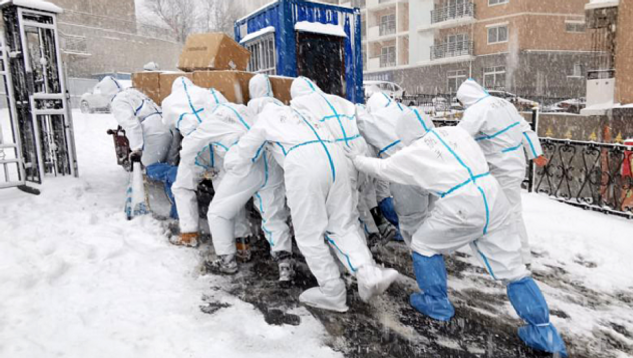 Members of an anti-epidemic volunteer team at Dalian Ocean University, northeastern China, deliver supplies to quarantined students and teachers.