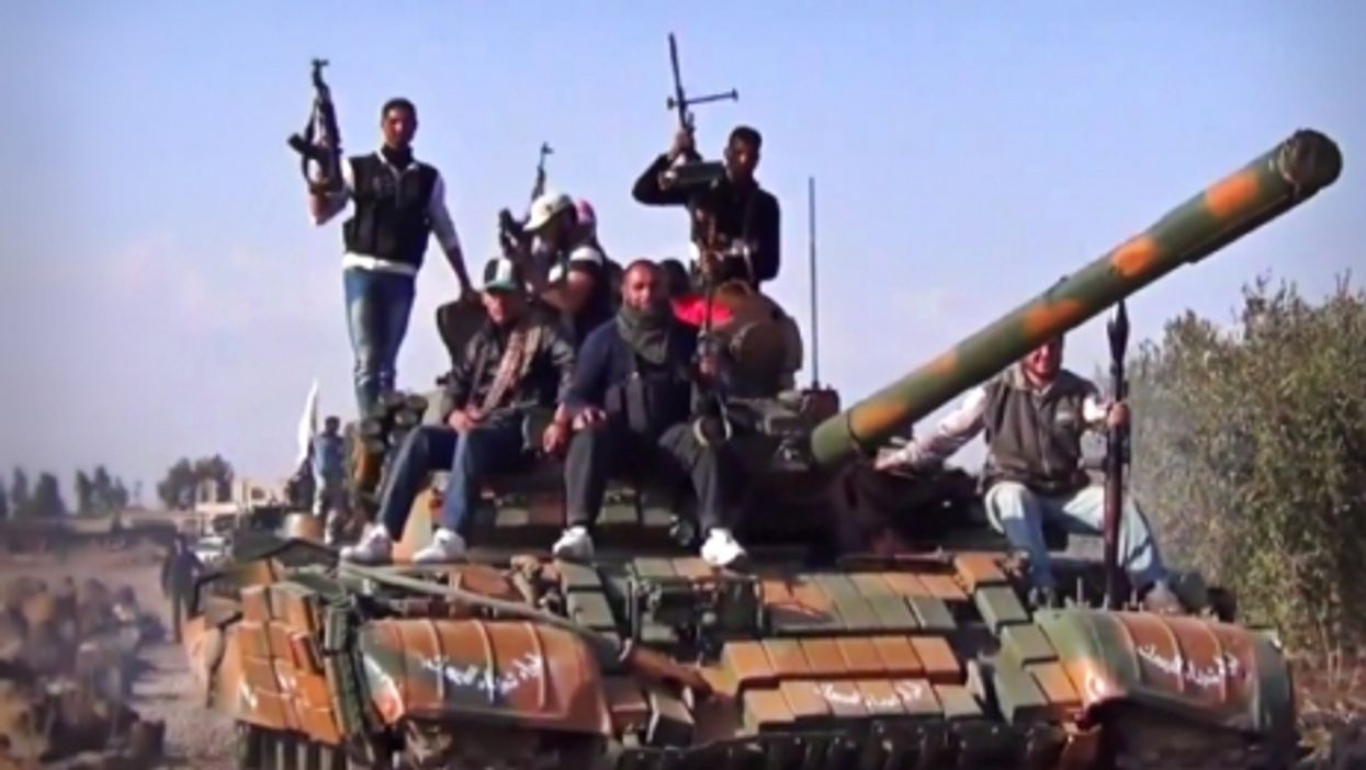 Members of the Yarmouk Martyrs Brigade parading on a tank