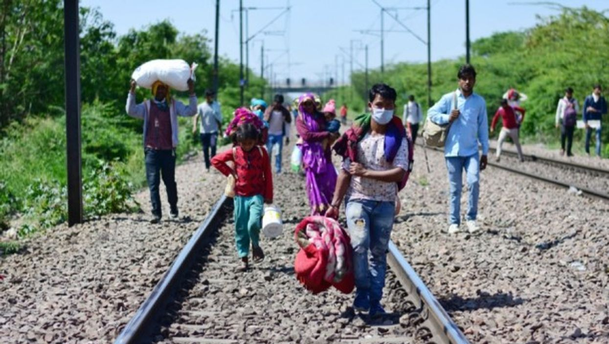 Migrant workers and their family members walking towards Laxmi nagar train station leaving India's capital for their villages, during the nationwide lock down.