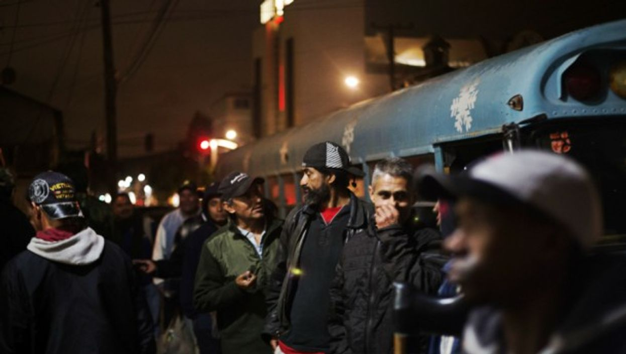 Migrants talking before they get into a shelter to rest, in Tijuana