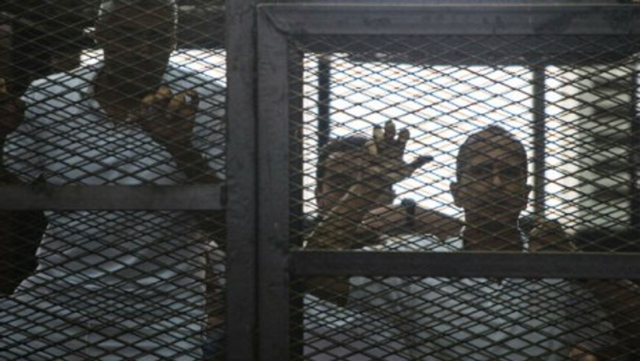 Mohamed Fadel Fahmy and Peter Greste listen to the verdict at a court in Cairo, June 23, 2014.