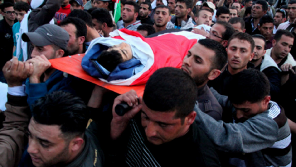 Mourners carry the body of a Palestinian teen killed by Israeli troops Wednesday.