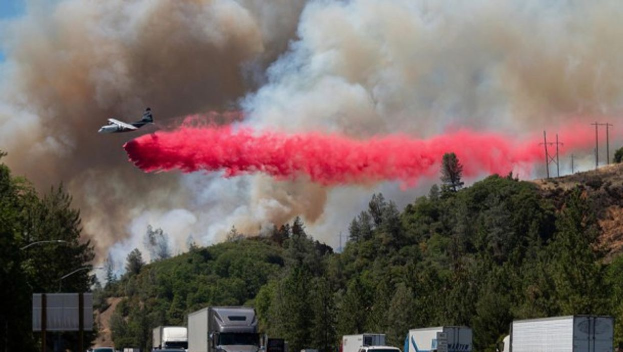 Near Lake Shasta, California, an air tanker releases fire retardant in an effort to extinguish the growing wildfire next to the northbound I-5 freeway. The U.S. Forest Service has ordered evacuations in the area.