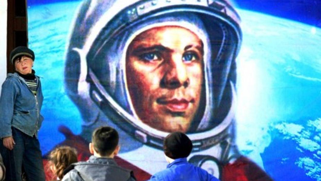 Near Russia's Baikonur cosmodromel, children examine an image of space pioneer Yuri Gargarin