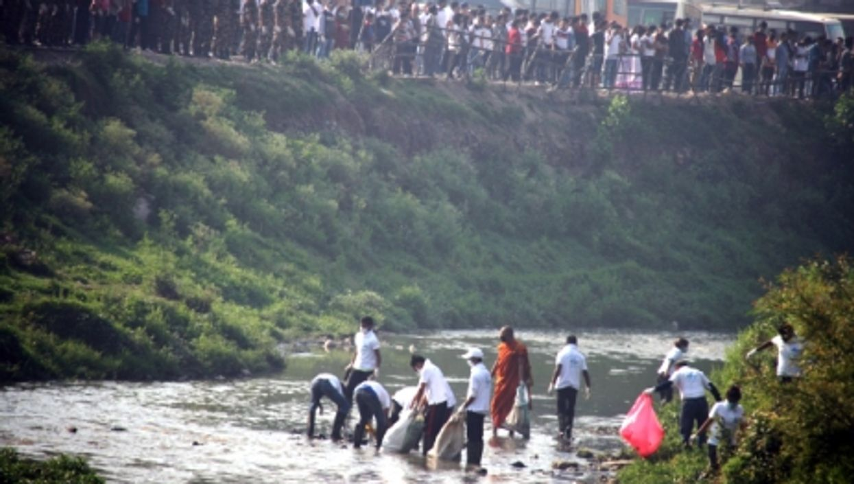 Nepalese people pick up rubbish on the Bagmati river on April 11, 2015.