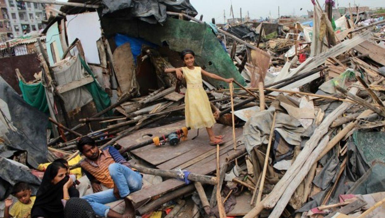 New Delhi residents outside demolished slum dwellings
