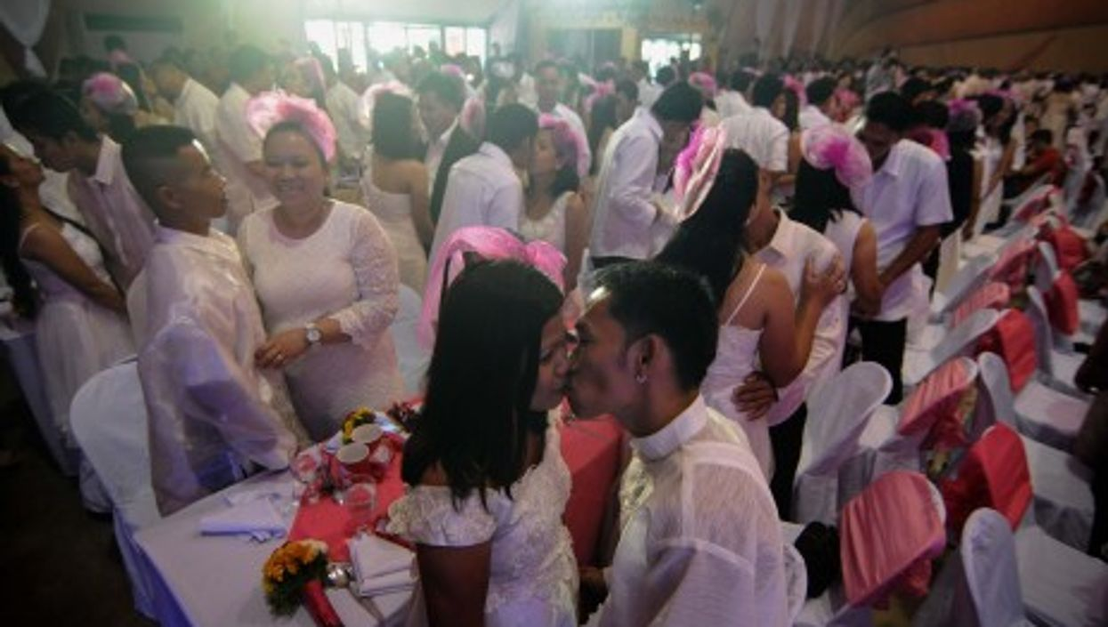 Newlywed couples kiss during a mass wedding ceremony in Manila on Valentine's Day.