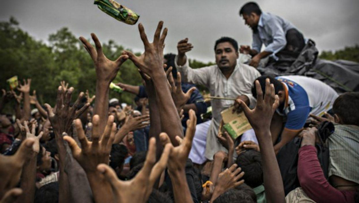 NGO workers distribute food to Rohingya refugees in Bangladesh