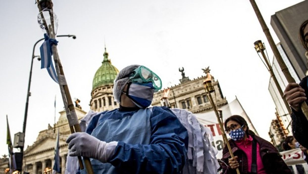 Nurses protesting in front of the Argentinian Congress during yesterday's International Nurses' Day. The pandemic continues to hit Argentina hard, with 24,475 new cases and 496 deaths reported on Tuesday.